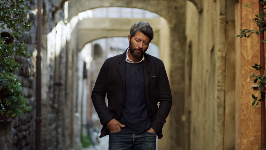In a quiet alleyway with stone buildings, an older attractive Italian male model walks and models his clothing.