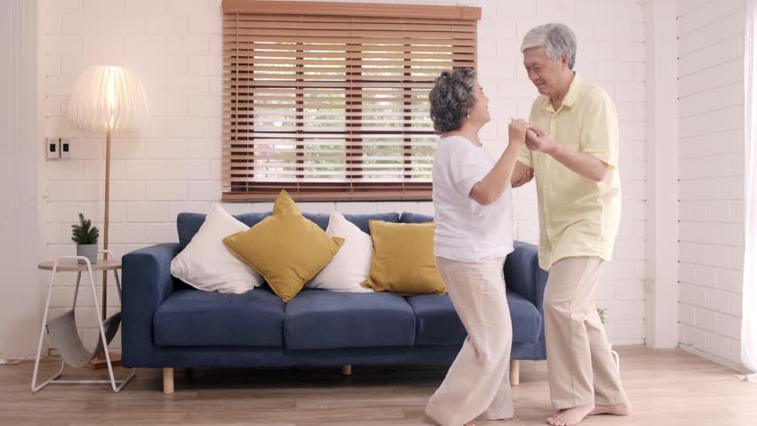 Asian elderly couple dancing together while listen to music in living room at home, sweet couple enjoy love moment while having fun when relaxed at home. Lifestyle senior family relax at home concept. | Shutterstock HD Video #1023392785