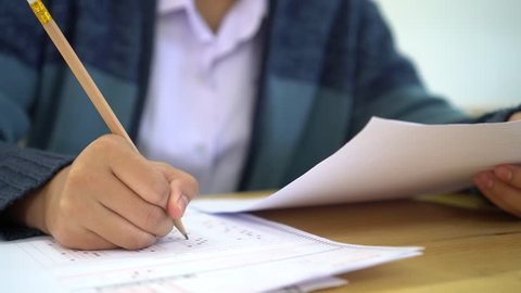 School / university Students hands taking exams, writing examination room with holding pencil on optical form answers paper sheet on desk doing final test in classroom. Education assessment Concept