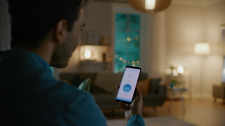 Young Handsome Man Gives a Voice Command to a Smart Home Application on His Smartphone and Lights in the Room are Being Turned On. It's a Cozy Evening. | Shutterstock HD Video #1023495715