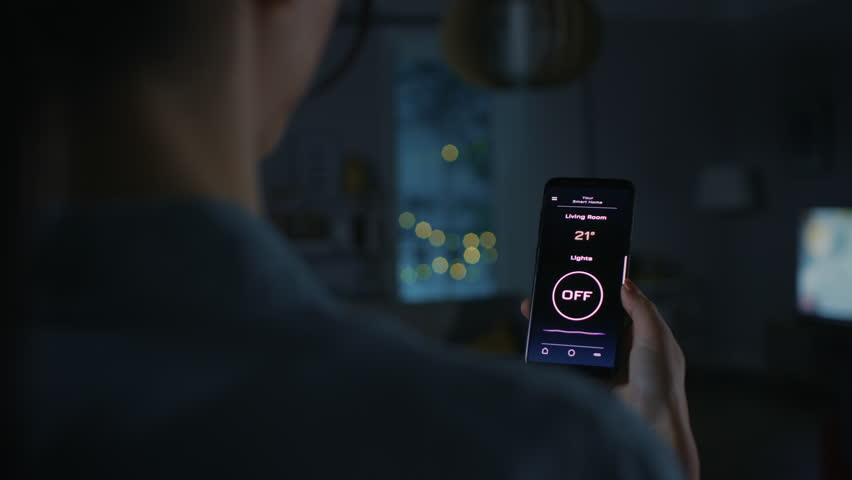 Young Beautiful Woman Gives a Voice Command to a Smart Home Application on Her Smartphone and Lights in the Room are Being Turned On. She Walks and Sits on a Couch. It's a Cozy Evening. | Shutterstock HD Video #1023495835