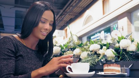 Young attractive Asian girl, ladyboy is smiling and using her smartphone while sitting at a table in a coffee shop