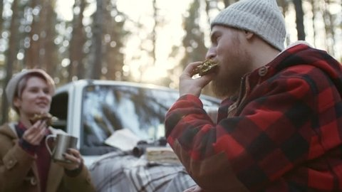 Medium shot of young man in beanie talking to girlfriend while eating sandwiches and drinking hot tea outdoors during car trip