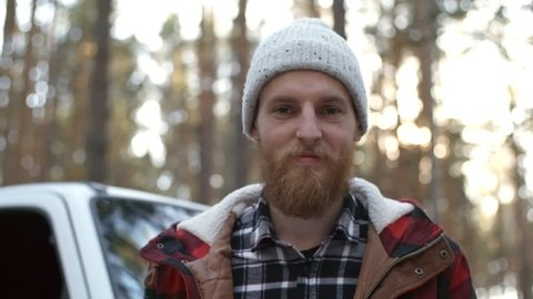 Medium shot of bearded young man in beanie holding paper map and looking at camera while standing by car on forest road