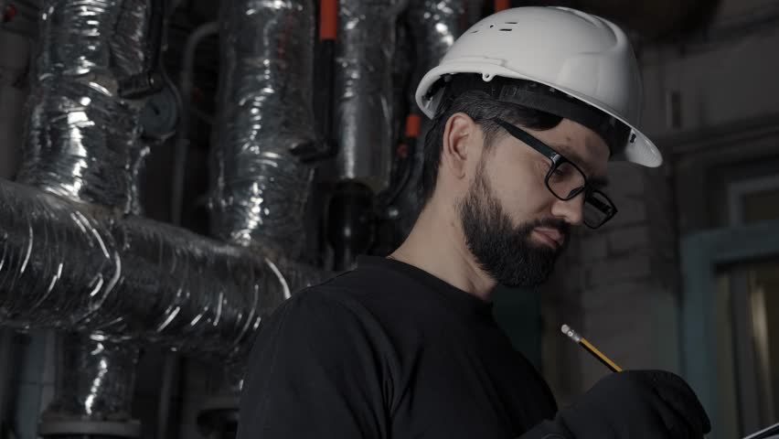 A young man in a white helmet, glasses and a black T-shirt looks straight into the camera, standing in a boiler room or a technical room with hot pipes. Portrait of an engineer or a locksmith.