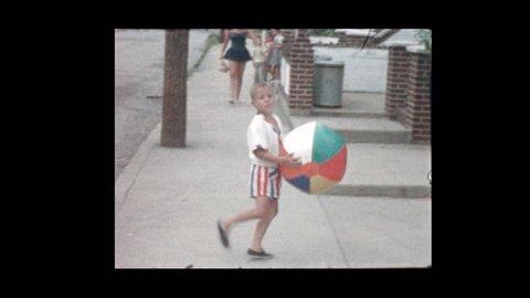 1956 Cute little boy with beach ball in street