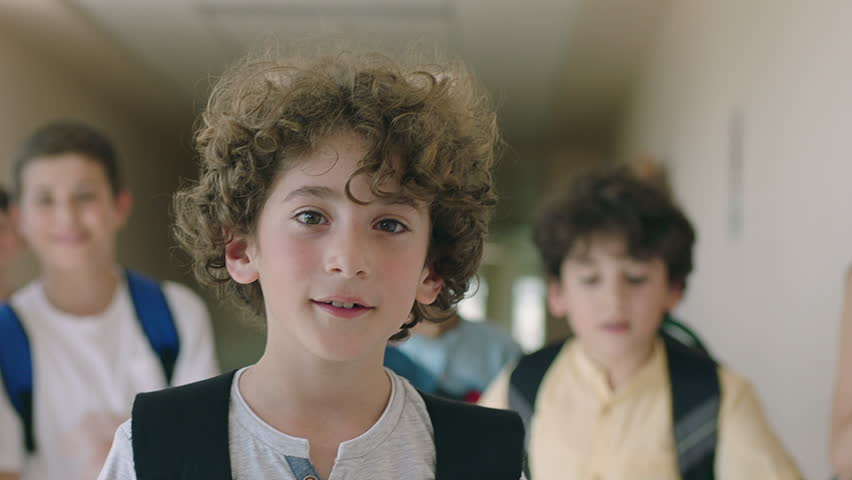 Close up portrait of beautiful , attractive , caucasian curly hair boy . Young boy looking and smiling on the camera inside school with friends . Portrait of children looks and smiles positive mood . | Shutterstock HD Video #1023585535