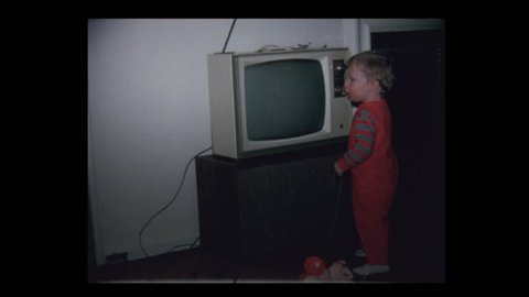 1971 Grandparents watching Baby boy and vintage television set