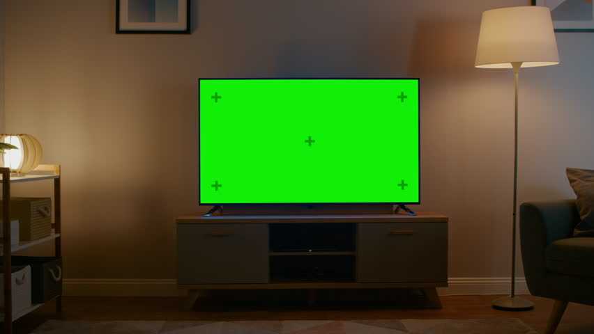 Zoom Out Shot of a TV with Horizontal Green Screen Mock Up. Cozy Evening Living Room with a Chair and Lamps Turned On at Home. | Shutterstock HD Video #1023697375