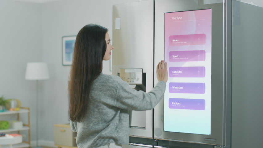 Beautiful Young Girl Walks Over to a Refrigerator While Drinking Her Morning Coffee. She is Checking the Weather Forecast and a To Do List on a Smart Fridge at Home. Kitchen is Bright and Cozy. #1023697405