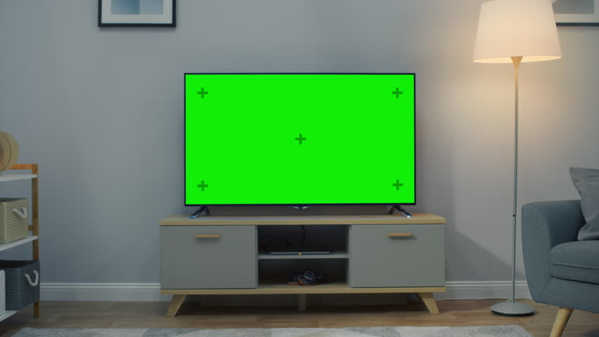Zoom Out Shot of a TV with Horizontal Green Screen Mock Up. Cozy Living Room at Day Time with a Chair and Lamps Turned On at Home. | Shutterstock HD Video #1023697465
