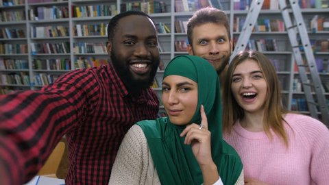 Carefree international diverse university students with beaming smiles, having fun posing for selfie shot in modern library. Joyful mischievous college friends taking self portrait photo on cellphone.