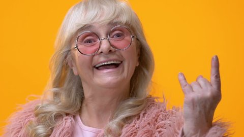 Positive granny showing rock n roll hand sign on bright background, feeling cool