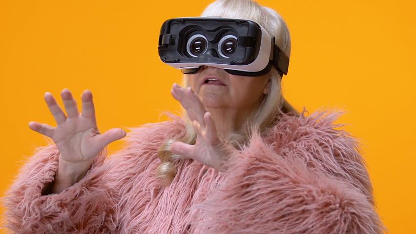 Funny senior woman in virtual reality goggles yellow background, entertainment