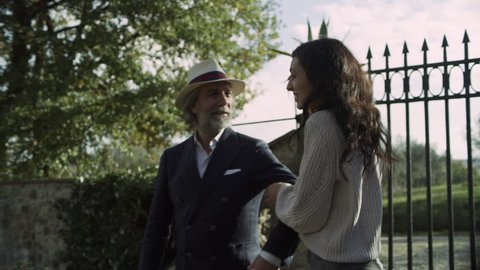 Loving Italian couple walking together through a gate into a garden. Wide shot on 8k helium RED camera.
