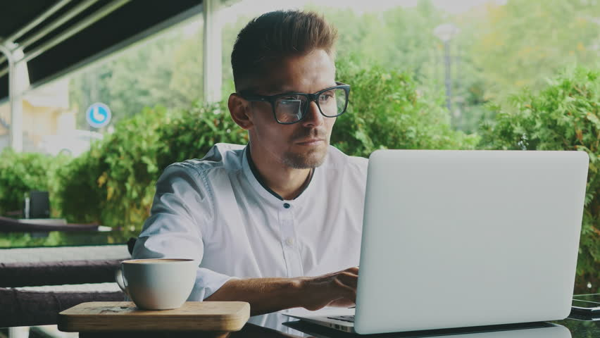 Young businessman dressed in business and glasses sitting in a cafe. | Shutterstock HD Video #1023806395