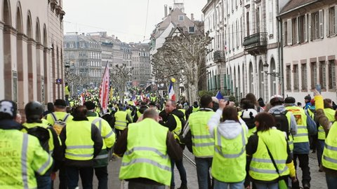 STRASBOURG, FRANCE - FEB 02, 2018: Rear view of thousands of Gilets Jaunes Yellow Vest manifestation on the 12 Saturday of anti-government demonstrations walking to Place Broglie
