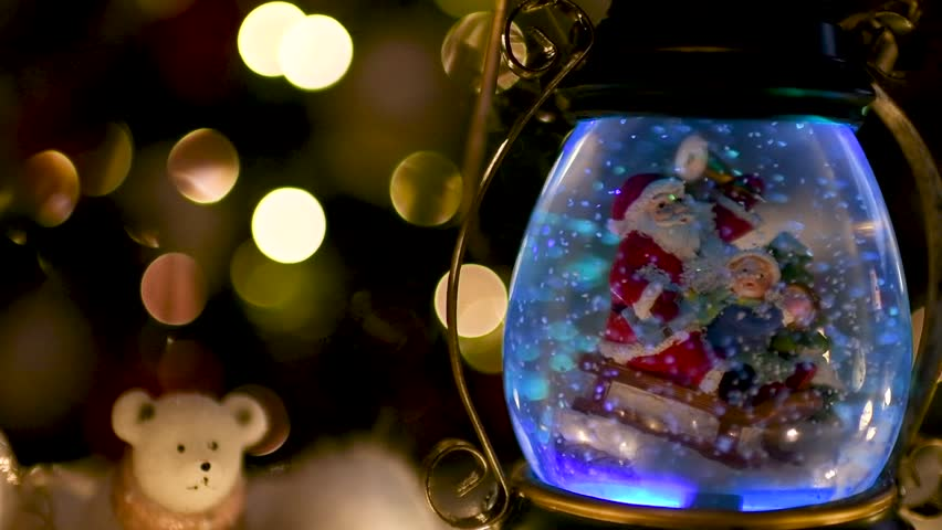 Cute snow globe with Santa Claus and children with Christmas lights blurred in the background. Flat plane