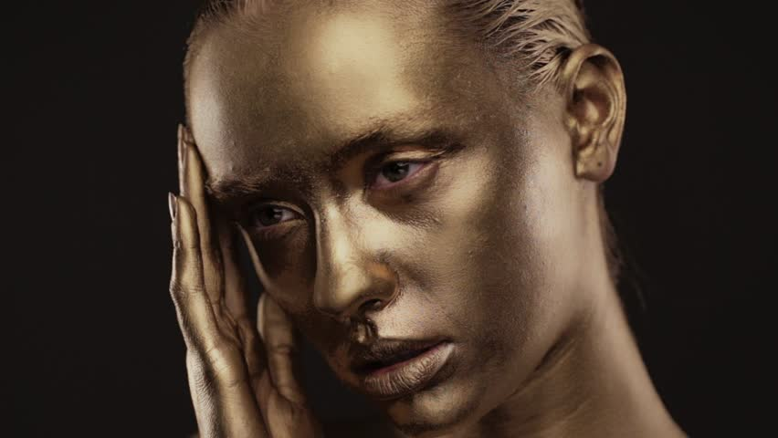 Beautyful girl with gold glitter on her face.Art image beauty face. Picture taken in the studio on a black background. | Shutterstock HD Video #1023908515