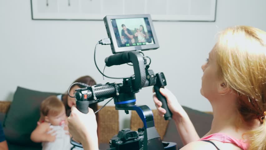 Video shooting process. An operator with a steadicam shoots a story about a family, mom and dad with a little girl on a cozy home sofa, who chat among themselves | Shutterstock HD Video #1023909475