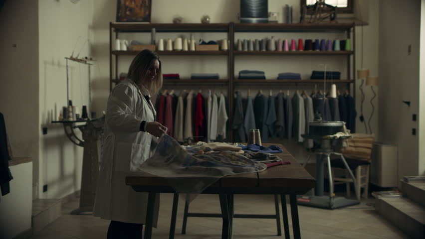 An Italian seamstress walks into a sewing workshop towards a table with fabrics and starts looking at them. Wide shot on 8k helium RED camera.