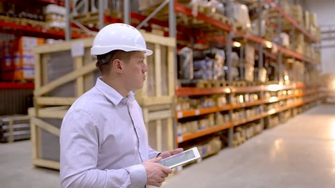 employee male warehouse worker engineer man in hard hat working at construction site warehouse, walking in logistics center factory, engineer using tablet computer, architect businessman man indoors