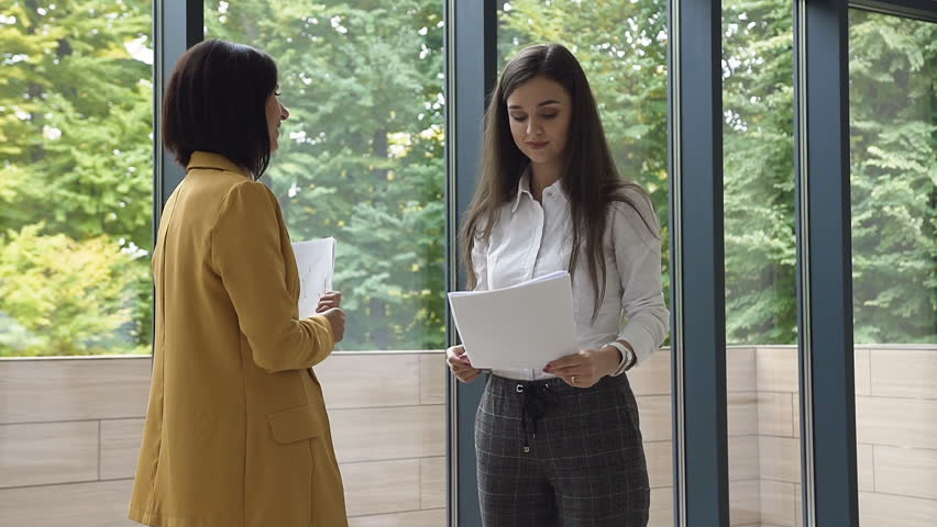 Two young successful business woman dressed in strict clothes for deal , shaking hands while, greeting one another before meeting or summit at office near windows with view of green park, slow motion | Shutterstock HD Video #1023990065