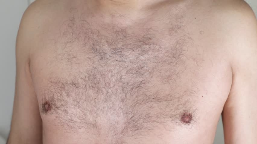 Closeup of a caucasian man trimming the hair of his body with an electric trimmer | Shutterstock HD Video #1024009805