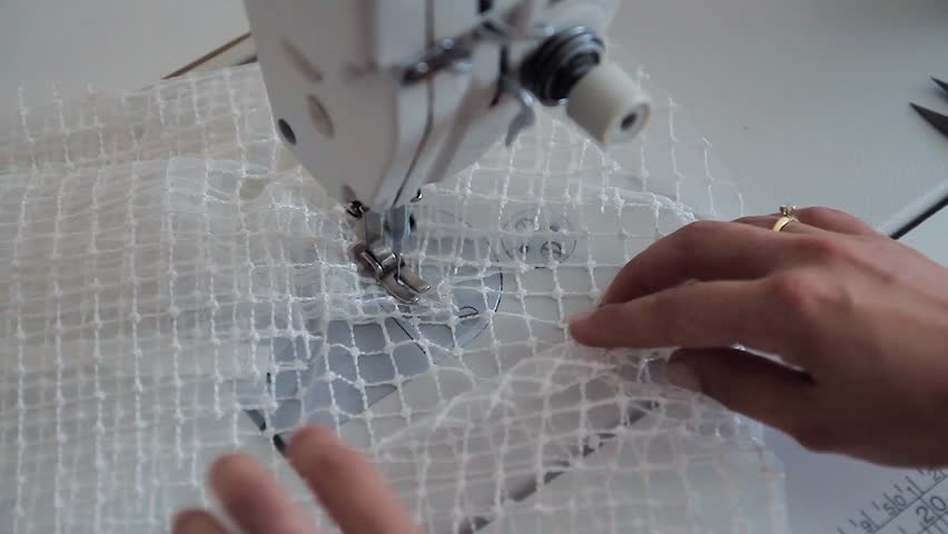 A woman working on a sewing project as she cuts fabric and sews it on a machine. sewing machine close up A hand of a dressmaker supporting a cloth while sewing on a machine. | Shutterstock HD Video #1024035185