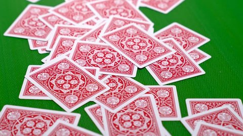 Pushing a pile of red backed poker cards into frame before collecting it back in 4K