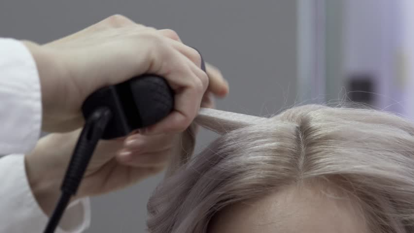 Close-up Of The Hand Of A Master Hairdresser Doing Styling Beautiful Curls With The Help Of Iron Curling On Blond Long Hair. Concept Of Beauty Salon And Hairdresser