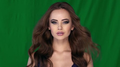 Beautiful  girl with wind blows  long hair . Attractive young woman with pretty face and wave brown hairstyle -  looking at camera. Slow motion.