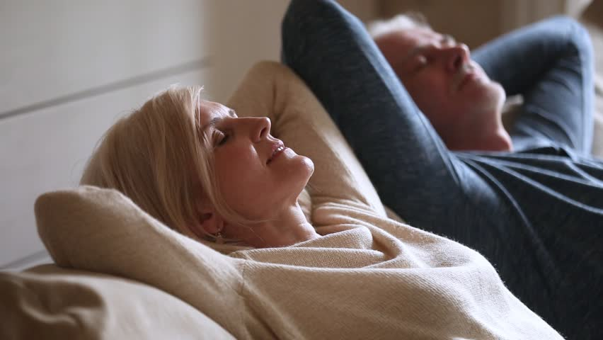 Calm senior middle aged couple relaxing leaning on comfortable soft couch having healthy nap together, happy old mature man and woman enjoy satisfaction chill feeling no stress free resting at home | Shutterstock HD Video #1024094015