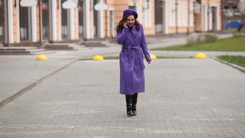 Full lenght of trendy brunette woman with bright lips wearing purple coat, beret and black high boots. She is walking along the street and talking to friend on the phone. Smiling. | Shutterstock HD Video #1024110065