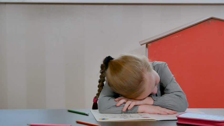 Tired and bored little preschool girl sleep on homework desk. Pretty female pupil do homework and school exercises. Home education concept | Shutterstock HD Video #1024112225