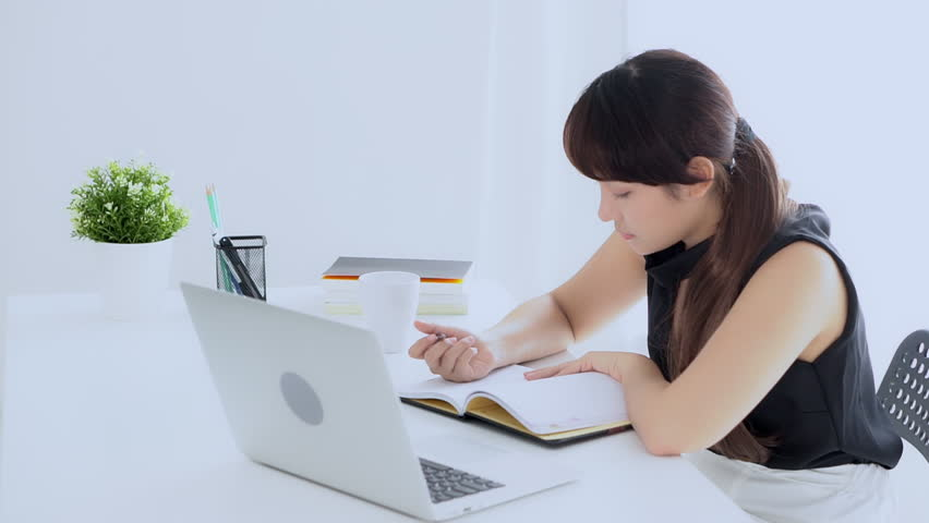 Beautiful asian woman smiling sitting in the living room study and learning writing notebook and diary at home, girl homework, business woman working with laptop computer on table, education concept | Shutterstock HD Video #1024113665