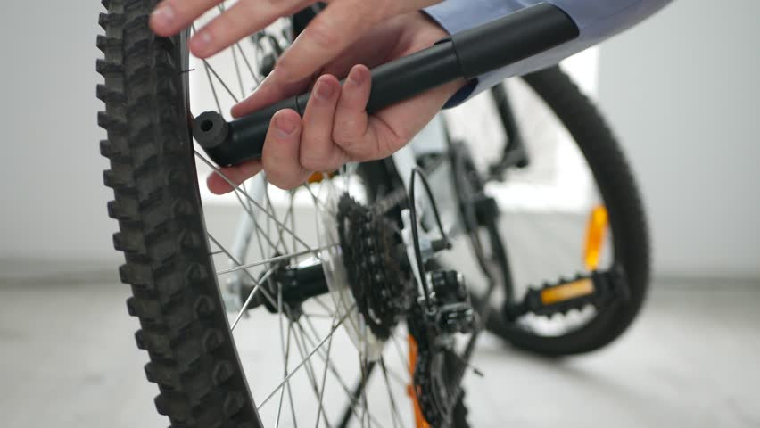Man Pumping Air in a Tire Preparing Bicycle for Sale in a Sports Shop | Shutterstock HD Video #1024139135