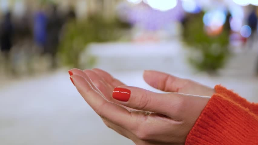 Female hands holding a conceptual hologram with ultra laptop. Woman with red nails and sweater with future holographic technology on a blurred background of the street | Shutterstock HD Video #1024152845