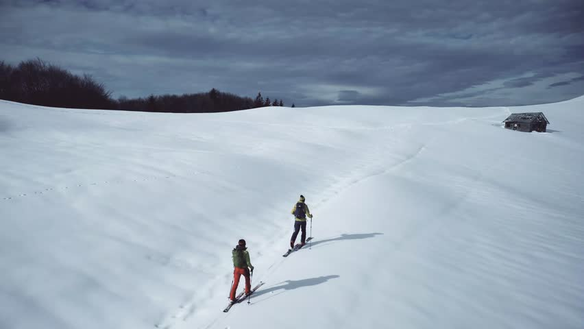 4k aerial footage of couple ski touring on a beautiful winter day on a high mountain plateau with old abandoned cabin in background  #1024160405