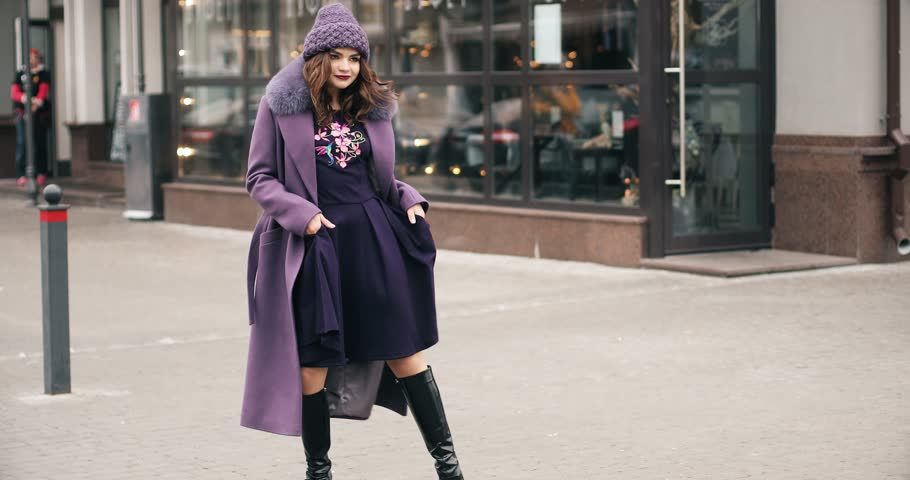 Full length footage of gorgeous fashionable lady in lilac winter hat and coat with fur collar, black high boots and deep purple dress dancing and having fun in the street of urban city. | Shutterstock HD Video #1024166855