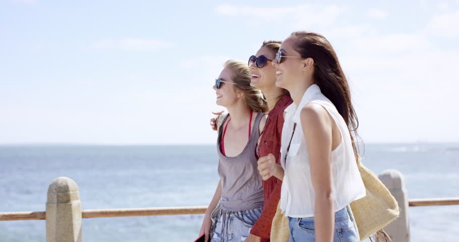 Three young women tourists on summer vacation walking on beach promenade wearing denim shorts