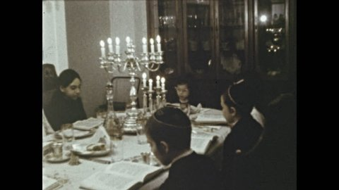 1970s: Family at dining table read from Torah. Man stands with chalice of wine near boy with candle. Family gathers around man. Man smells chalice and passes it to children. Children smell chalice.