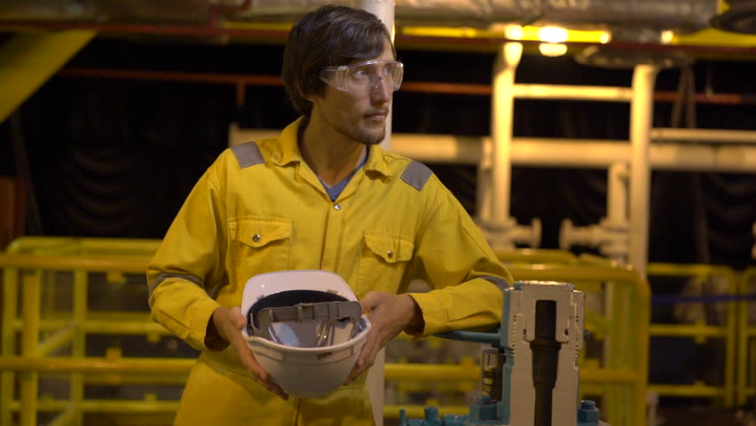 Young man in a yellow work uniform, glasses and helmet in industrial environment,oil Platform or liquefied gas plant. Slowmotion shot