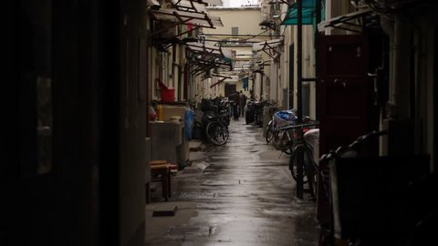 SHANGHAI - MARCH 20, 2018: Small back street between residential buildings at Nanjing East Road residential district. Wet pavement at drizzling weather, rat run towards at passage