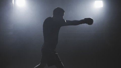 Muay thai fighter punching in smoky studio. Kickboxer training in low light gym in slow motion. Silhouette on dark background