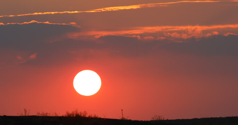 Time lapse Beautiful big sunrise orange Sunset Puffy fluffy dark cloud large yellow sun 4K video for editing big setting sun Bright sun appearance in sky between dark clouds Outlines shines fluff warm