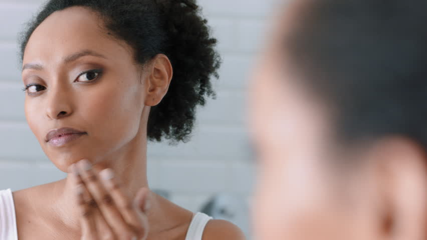 Portrait beautiful african american woman looking in mirror at perfect skin enjoying natural complexion getting ready at home | Shutterstock HD Video #1024428005