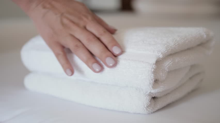 Close-up of hands putting stack of fresh white bath towels on the bed sheet. Room service maid cleaning hotel room macro closeup | Shutterstock HD Video #1024445465