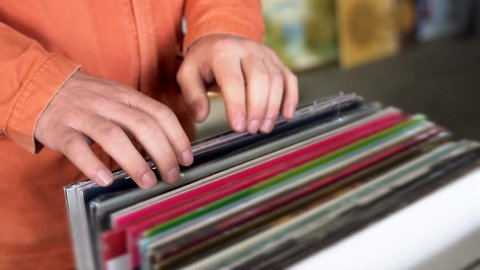man looking at old vinyl records at flea market
