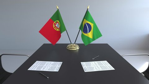 Flags of Portugal and Brazil and papers on the table. Negotiations and signing an international agreement. Conceptual 3D animation